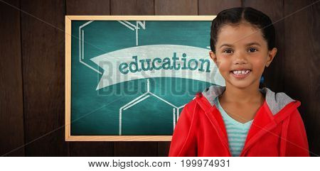 Portrait of smiling girl holding digital tablet against education against green chalkboard