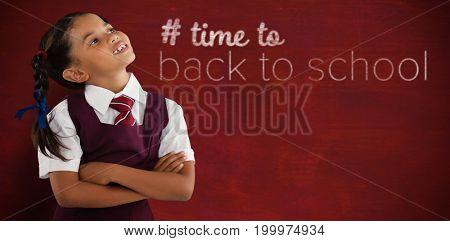 Thoughtful schoolgirl looking away against brown blackground