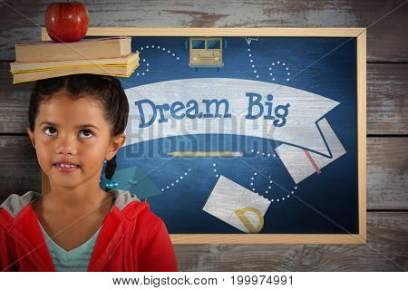 Girl balancing books and apple on head against dream big against blue chalkboard