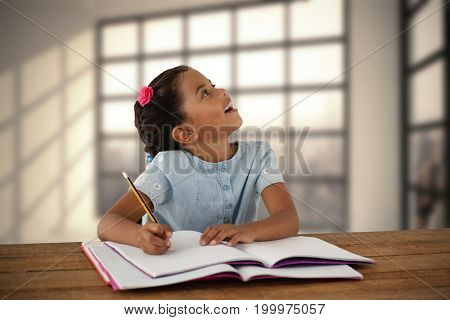 Girl looking up while writing in book against room with large window showing city