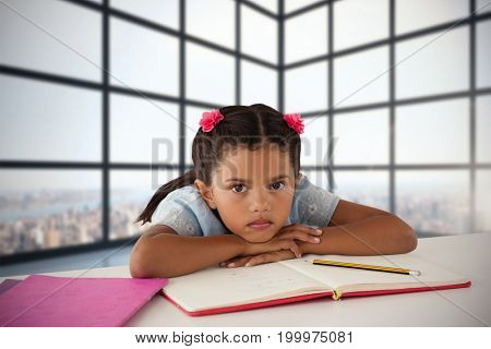 Girl leaning on open book at desk against room with large windows showing city