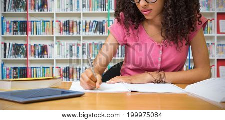 Student sitting in library writing against multi colored bookshelf in library