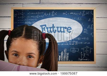Schoolgirl covering mouth with book against future against blue chalkboard