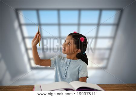 Girl looking at pencil while sitting at desk  against room with large windows showing city