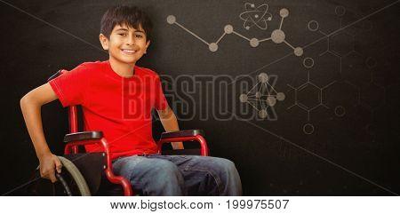 Portrait of boy sitting in wheelchair against blackboard