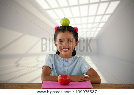 Smiling girl with Granny Smith apple on head against room with windows at ceiling