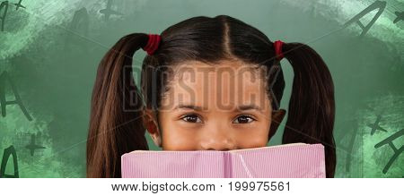 Schoolgirl covering mouth with book against green chalkboard