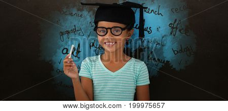 Portrait of smiling girl wearing mortarboard and holding chalk against blackboard