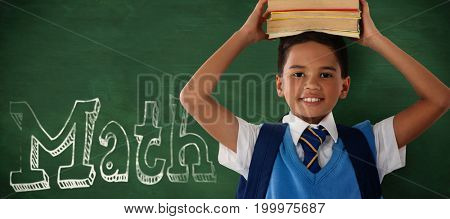 Smiling schoolboy carrying books on head over white background against green background