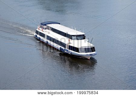 White passenger ship slow float sails on a river in summer day top view