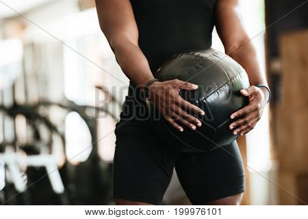 Cropped image of african sports strong man make sport exercise with ball.