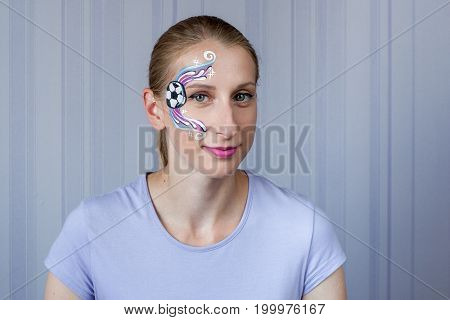 Young woman with face painting football fan mask