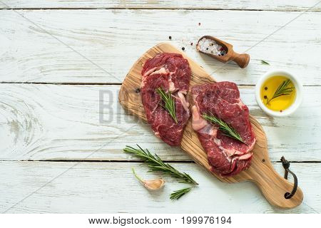 Fresh meat. Beef steak with ingredients at cutting board. Top view with copy space.
