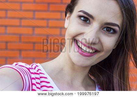 Beautiful urban woman taking picture of herself selfie.