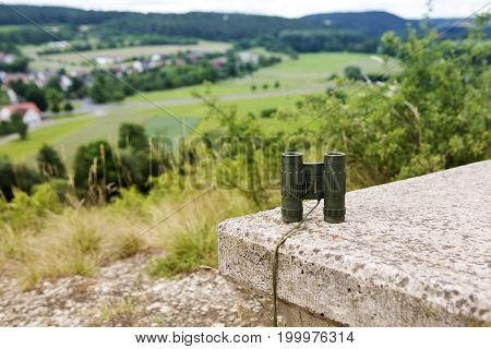 binoculars on a stone bench with view of a small town in the valley