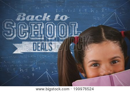 Schoolgirl covering mouth with book against blue background