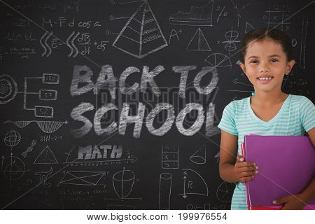 Portrait of smiling girl holding files against black background