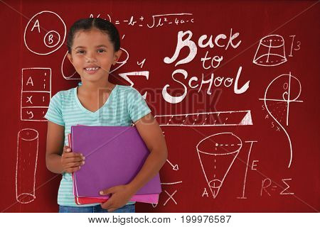 Portrait of smiling girl holding files against blackboard with copy space on wooden board
