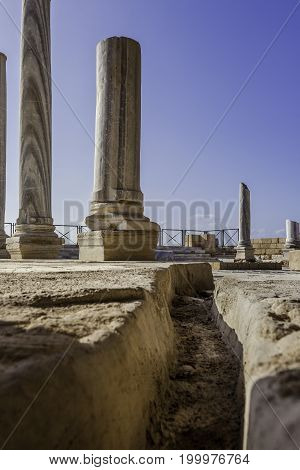 Doric white marble columns remnants from low angle with sewer drain in floor Caesarea national park