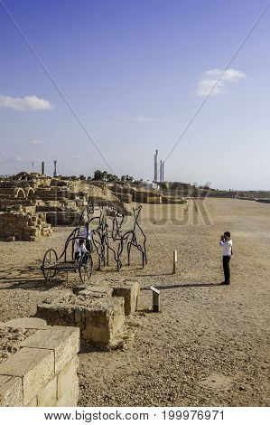 Hasidic family father taking picture of children on horses and carriage statue at Caesarea national park hippodrome