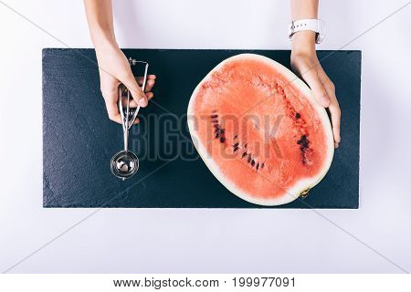 Female Hands Hold Half A Ripe Watermelon And A Scoop For Ice Cream