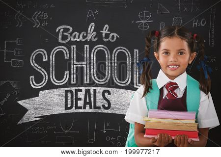 Smiling schoolgirl carrying books against black background