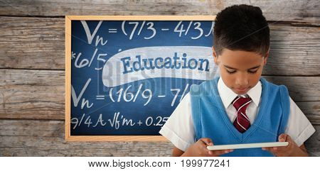 Schoolboy using digital tablet against education against blue chalkboard