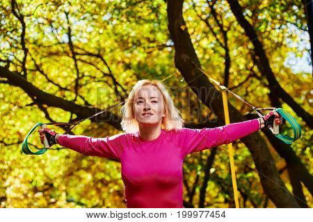 Portrait of beautiful smiling sportswoman doing resistance training in park