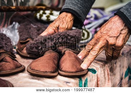 Old wrinkled female hands hold children's shoes at the flea market in the Caucasus