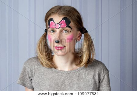 Young woman with face painting pink bow mask