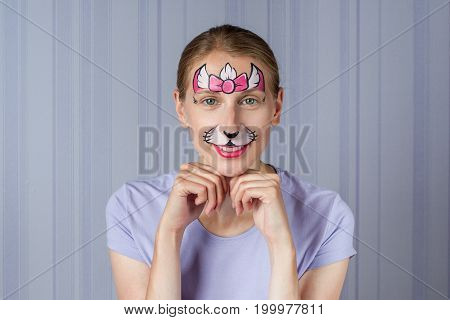 Young woman with face painting pink kitty cat mask