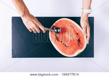Female Hand Slices Watermelon With A Spoon On A White Table