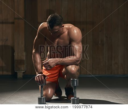 Young sportsman preparing to do push up with dumbbells in the gym