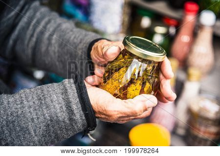 Old wrinkled hands hold a jar with mountain jam from the leaves of Caucasian trees leaves in the mountains