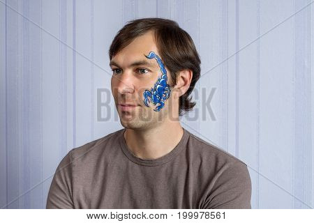 Young man with face painting blue Scorpio mask