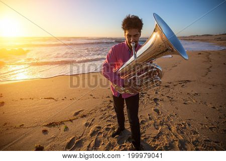 Musician play to musical instrument Tuba on ocean shore.