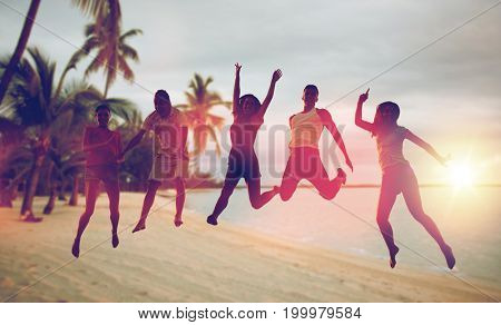 summer holidays, fun and people concept - group of happy friends dancing and jumping over exotic tropical beach with palm trees background