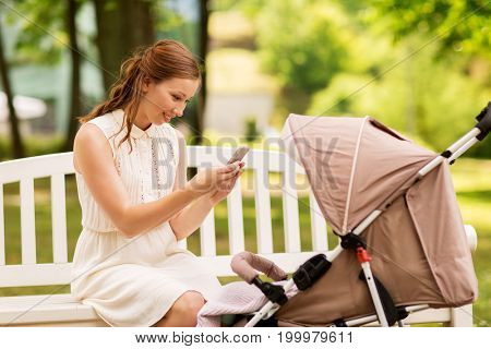 motherhood, technology and people concept - happy mother with smartphone taking picture of her baby stroller at summer park