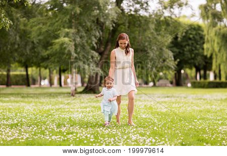 family, childhood and parenthood concept - mother with little baby girl walking at summer park