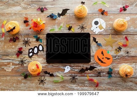 holidays, technology and party concept - halloween decorations and treats with tablet pc computer on wooden boards background