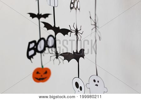 holidays and decoration concept - halloween paper party  decorations over white background