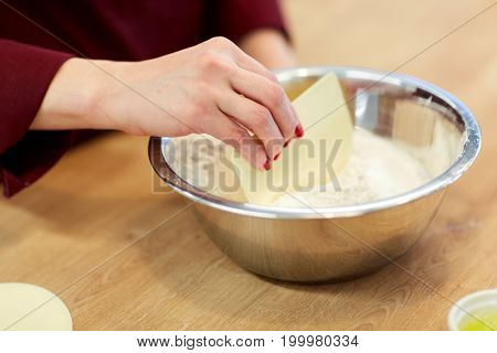 cooking food, baking and people concept - chef with spatula stirring flour in bowl and making batter or dough