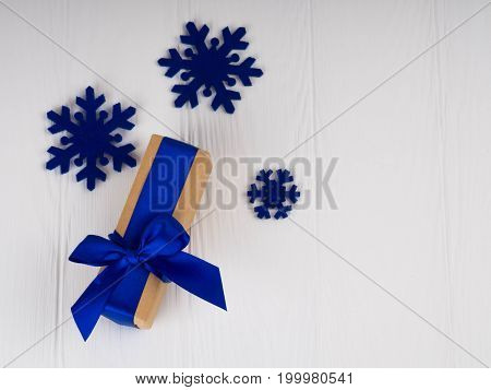 new Christmas gift with blue ribbon, bowknot, next blue snowflakes. On white wood background, copy space for text