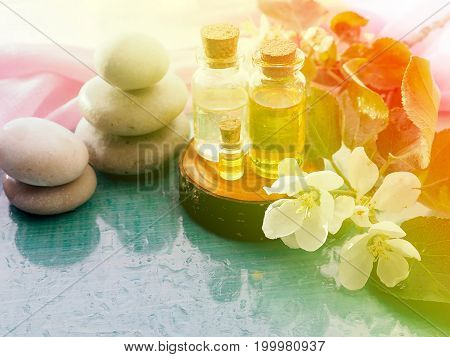 the bottle of oil, a plant extract, the concept of health, beauty, youth, non-traditional medicine. Next to stones for massage, aromatic salt, flowers