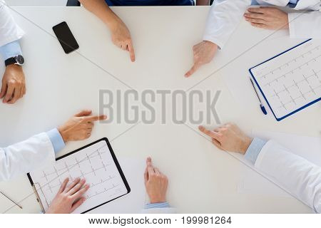 medicine, healthcare and cardiology concept - group of doctors with cardiograms, clipboards and laptop computer showing something imaginary on table