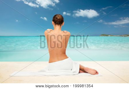 beauty, spa, people and bodycare concept - beautiful young woman in white towel with bare top from back over exotic tropical beach background