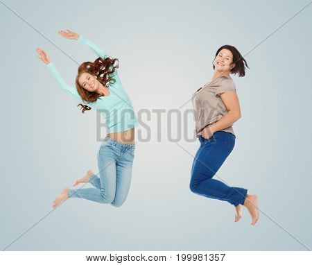 diverse, body positive and people concept - happy different age and size women jumping over blue background