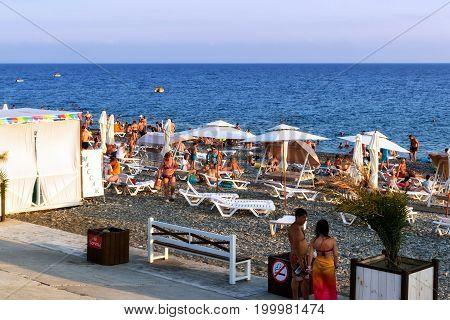 Tourists On The Beach Of The Black Sea Coast, Swim And Sunbathe On The Equipped Beach Hotel