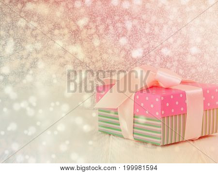 the gentle pink new Christmas gift with a nice ribbon, bowknot, white wood background, copy space for text, concept of the gift. holiday, gift, added a snow effect