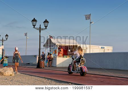 Tourists Walk And Ride On Electric Cycles And Bikes On The Promenade